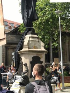 The statue was initially covered for the protest. Placard reading 'Colston Must Fall' at its base.