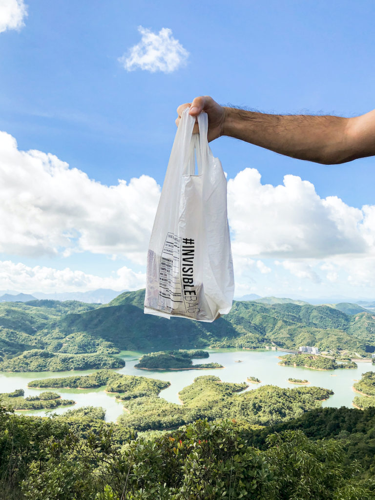 A picture of the #INVISIBLEBAG held up against the background of the beautiful view from a Hong Kong hiking trail